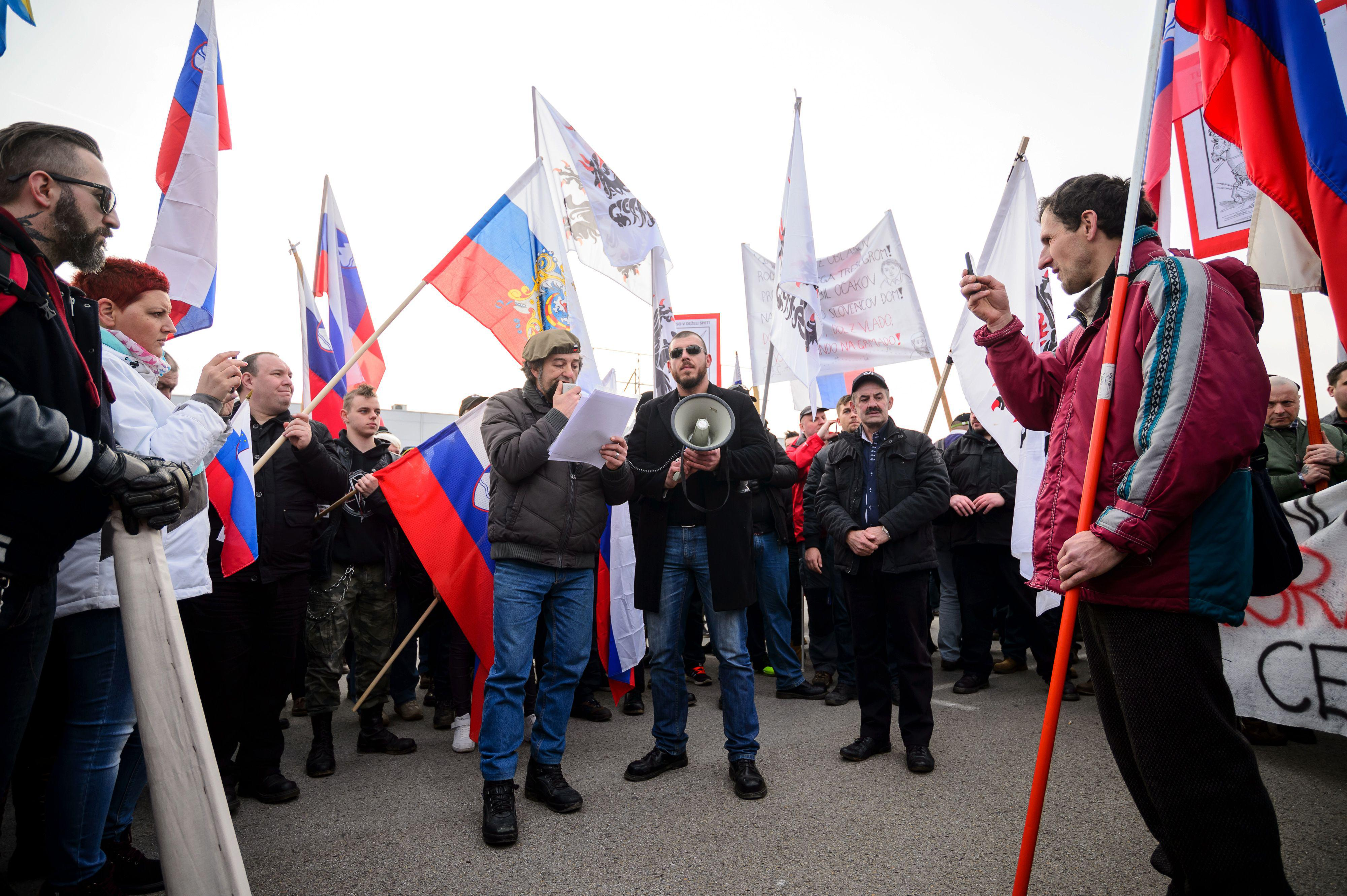 People wave Slovenian flags during a protest against the possible opening of a center for migrants in the vicinity of the town of Sencur, some 25km north of Ljubljana, on February 20, 2016. Slovenia said on February 14 that it would clamp down on the number of migrants allowed to enter the country, ahead of tougher measures set to be announced by neighbouring Austria later this week to slow down the influx. The country of nearly nine million people last year received 90,000 asylum claims, one of the bloc's highest rates per capita. / AFP / Jure Makovec/AFP
