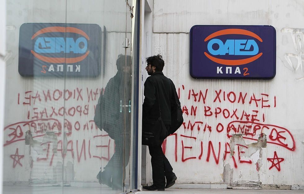 A man enters an office of Labor Force Employment Organization, with graffiti under the logo of OAED reading ''Snow or rain the jobless are always hungry'', in Athens, Thursday, March 1, 2012.  Europe's leaders travel to Brussels Thursday, hoping to chart the continent's way back to growth as figures showing unemployment in the 17-country eurozone spiking to its highest level since the euro was established in 1999.(AP Photo/Thanassis Stavrakis)