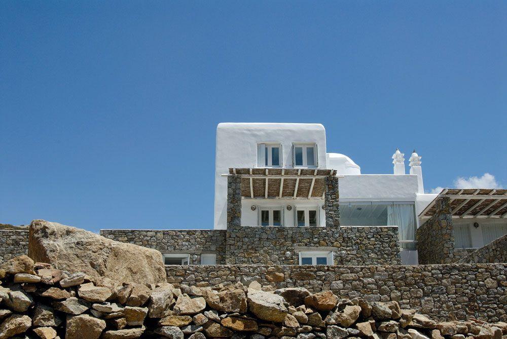 Μια λευκή εξοχική κατοικία εναρμονισμένη άψογα στο άγριο φυσικό τοπίο της Μυκόνου